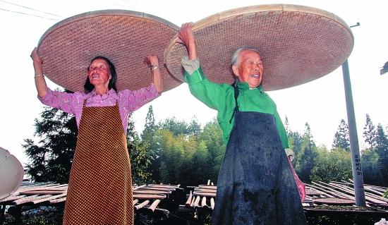 林好/▲夕阳西下,林好(右)和林富英忙着收晾晒的稻谷。顶着秋天的...